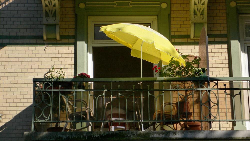 Balkonverschönerung durch einen knalligen Sonnenschirm